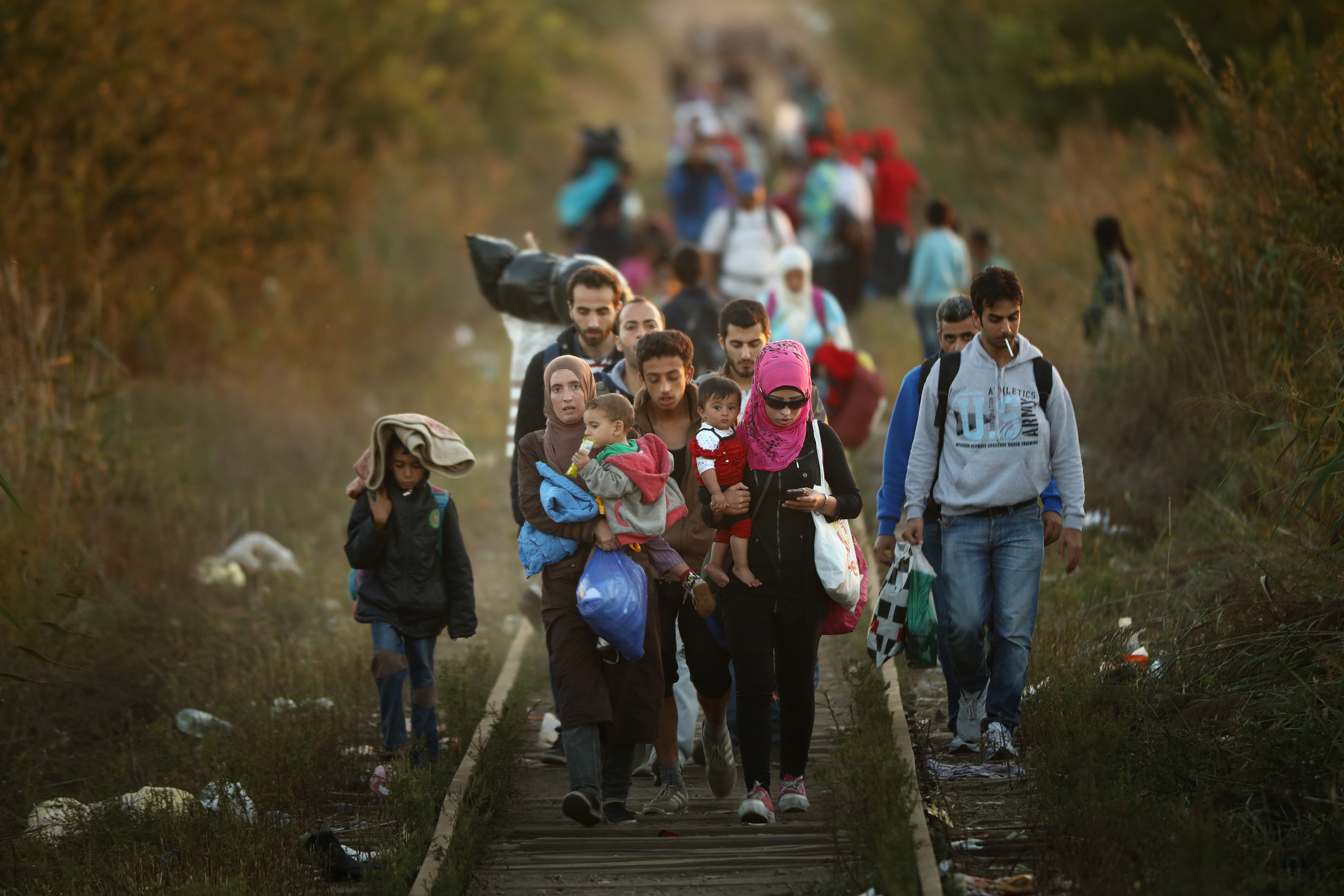 SUBOTICA, SERBIA - SEPTEMBER 09:  Migrants make their way through Serbia, near the town of Subotica, towards a break in the steel and razor fence erected on the  border by the Hungarian government on September 9, 2015 in Subotica, Serbia. Thousands of migrants have funnelled their way across country to the small gap in the steel fence unopposed by the authorities.  Since the beginning of 2015 the number of migrants using the so-called 'Balkans route' has exploded with migrants arriving in Greece from Turkey and then travelling on through Macedonia and Serbia before entering the EU via Hungary. The number of people leaving their homes in war torn countries such as Syria, marks the largest migration of people since World War II.  (Photo by Christopher Furlong/Getty Images)