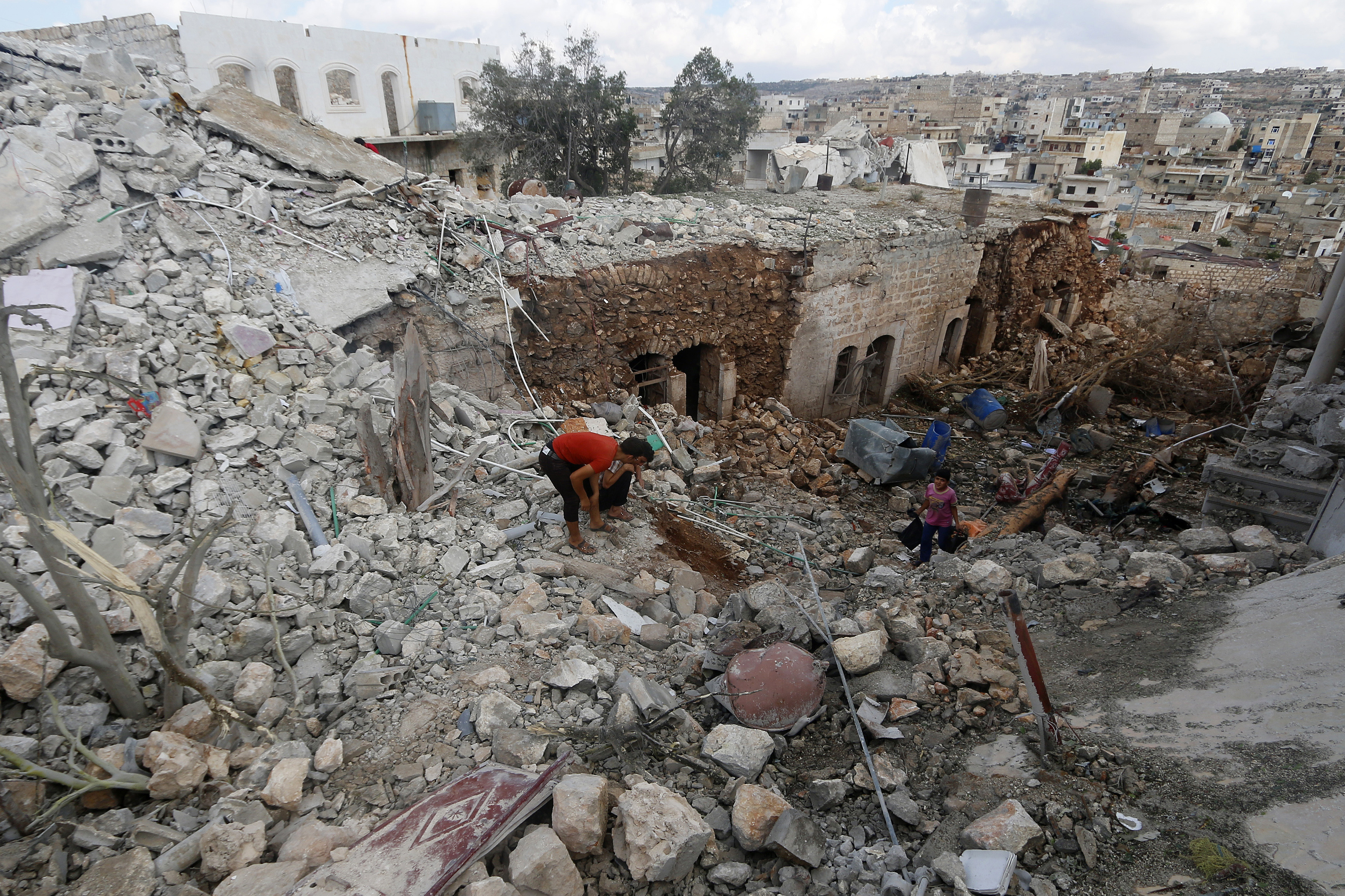 Civilians inspect a site hit by what residents said were airstrikes carried out by the Russian air force in the town of Darat Izza in the province of Aleppo, Syria, October 7, 2015. REUTERS/Ammar Abdullah - RTS6T8N