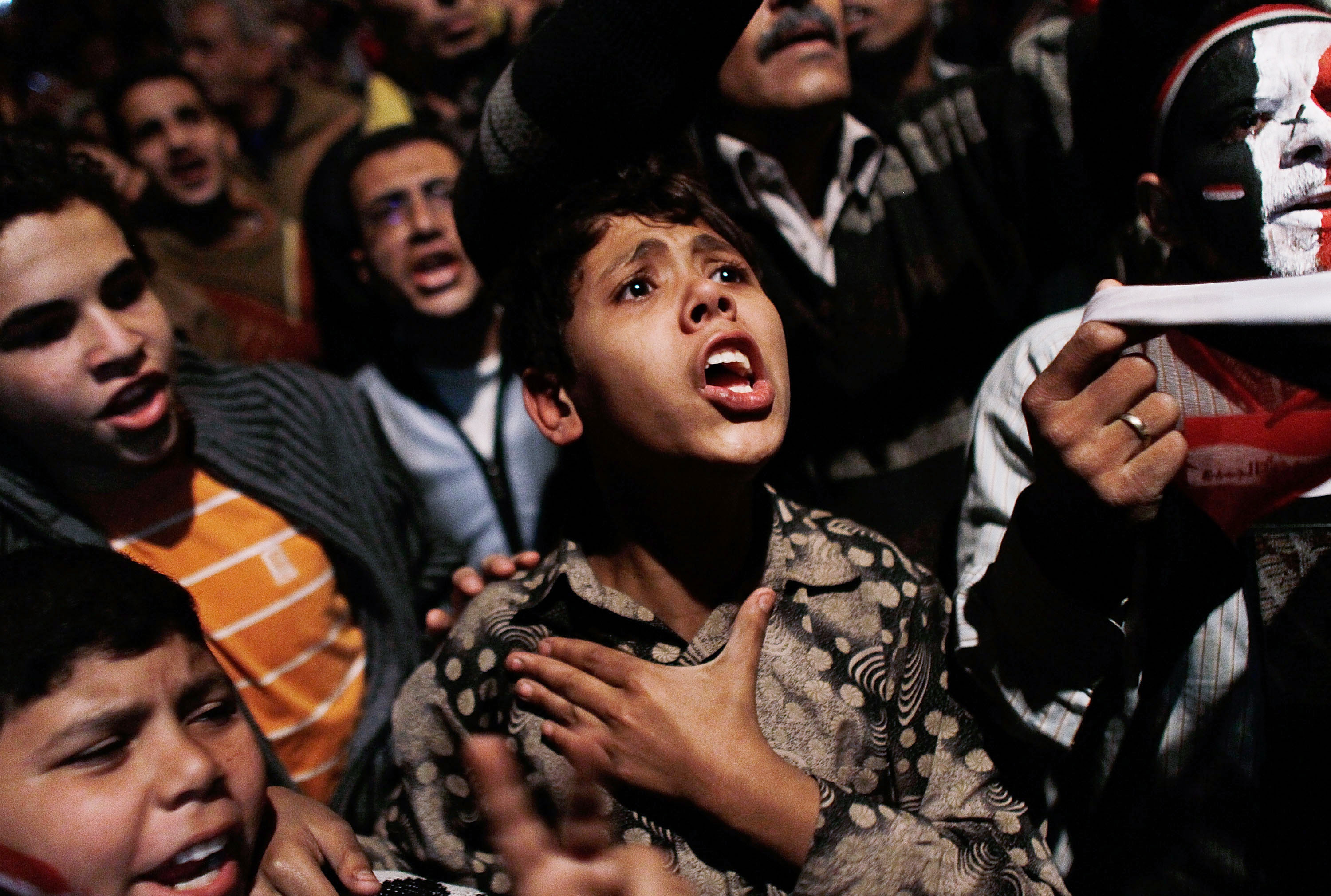 CAIRO, EGYPT - FEBRUARY 11:  A boy sings in Tahrir Square after it is announced that Egyptian President Hosni Mubarak was giving up power February 11, 2011 in Cairo, Egypt.  After 18 days of widespread protests, Egyptian President Hosni Mubarak, who has now left Cairo for his home in the Egyptian resort town of Sharm el-Sheik, announced that he would step down.  (Photo by Chris Hondros/Getty Images)