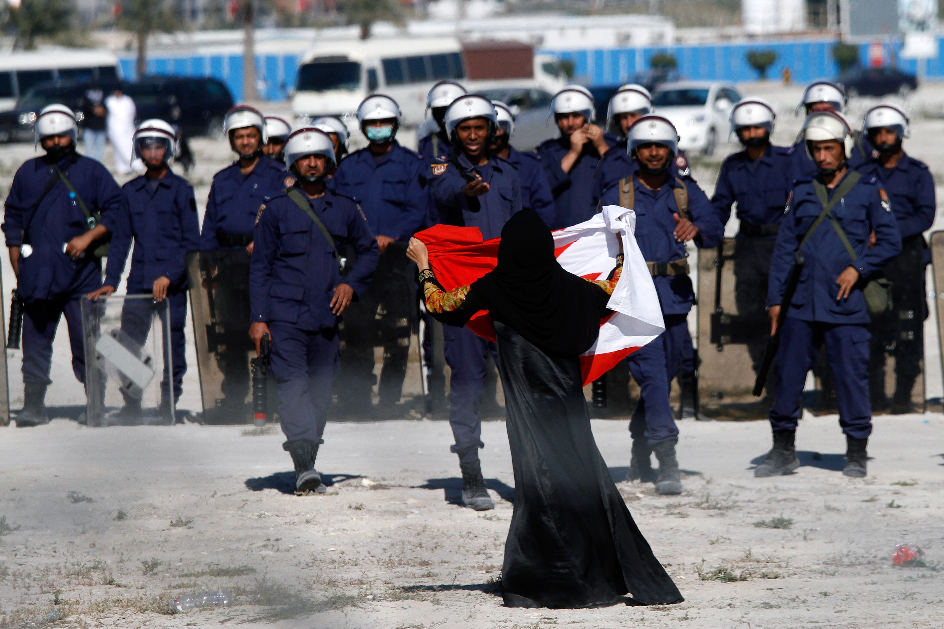 MANAMA, BAHRAIN - FEBRUARY 19:  An anti-government protestor gestures in front of police as demonstrators re-occupy Pearl roundabout on February 19, 2011 in Manama, Bahrain. Anti-government protesters were fired at with tear gas and rubber bullets as they marched to retake the roundabout, injuring several protestors at the site of two deadly previous confrontations between police and demonstrators. The Bahrain military has since backed off by order of Crown Prince Salman bin Hamad Al Khalifa, and instead police have been positioned to squelch the uprising.  (Photo by John Moore/Getty Images)
