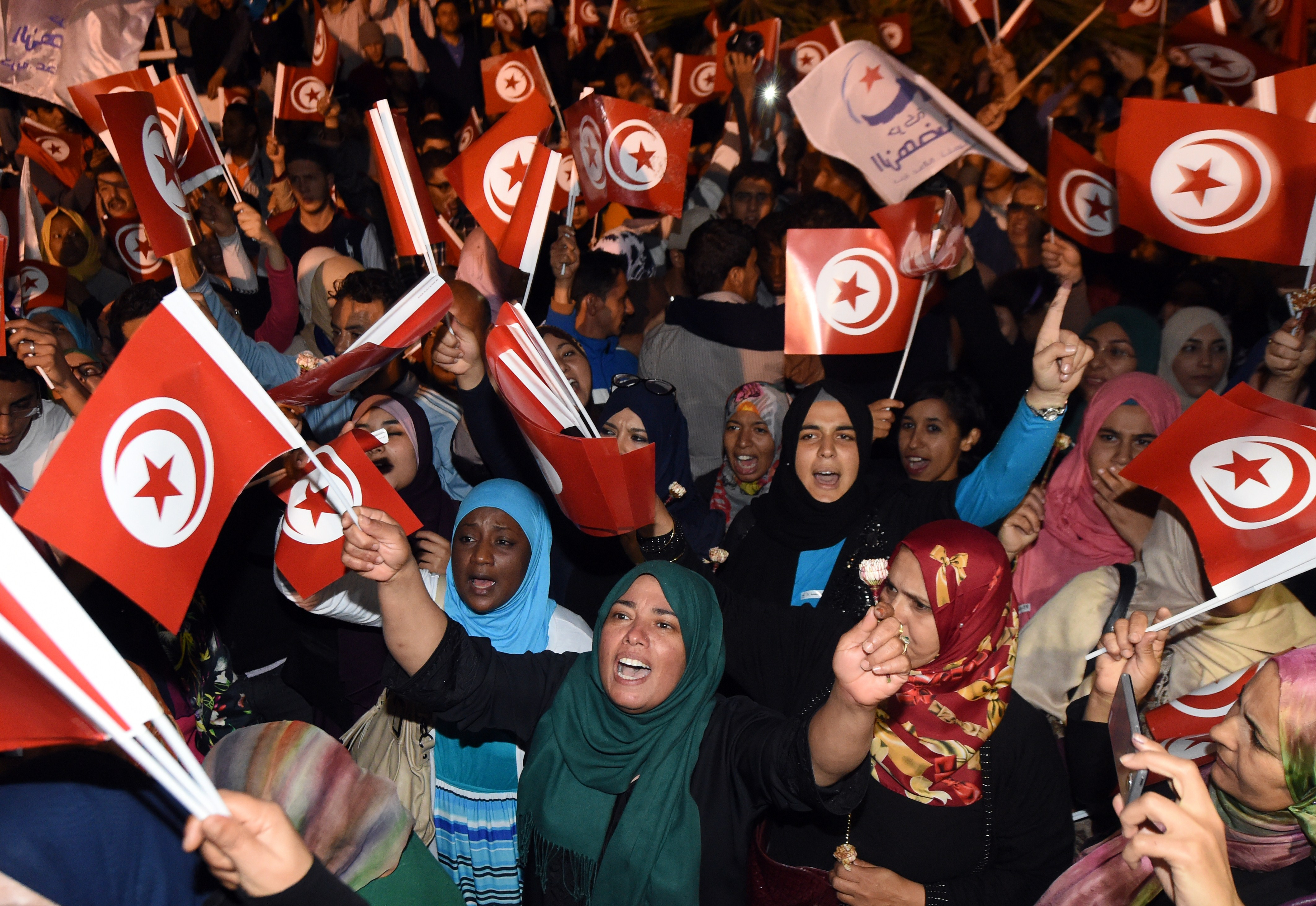 "Tunisian Ennadha Party supporters wave flags as they wait for the party's leader to give a speech on October 27, 2014 in Tunis following the legislative election. The leader of Tunisia's Islamist Ennahda party congratulated his secular rival on October 26 for ""his party's win"" in a general election seen as critical for democracy in the cradle of the Arab Spring. The first parliamentary election since Tunisia's 2011 revolution pitted Ennahda against secular opponent Nidaa Tounes, with an array of leftist and Islamist groups also taking part. AFP PHOTO / FADEL SENNA        (Photo credit should read FADEL SENNA/AFP/Getty Images)"