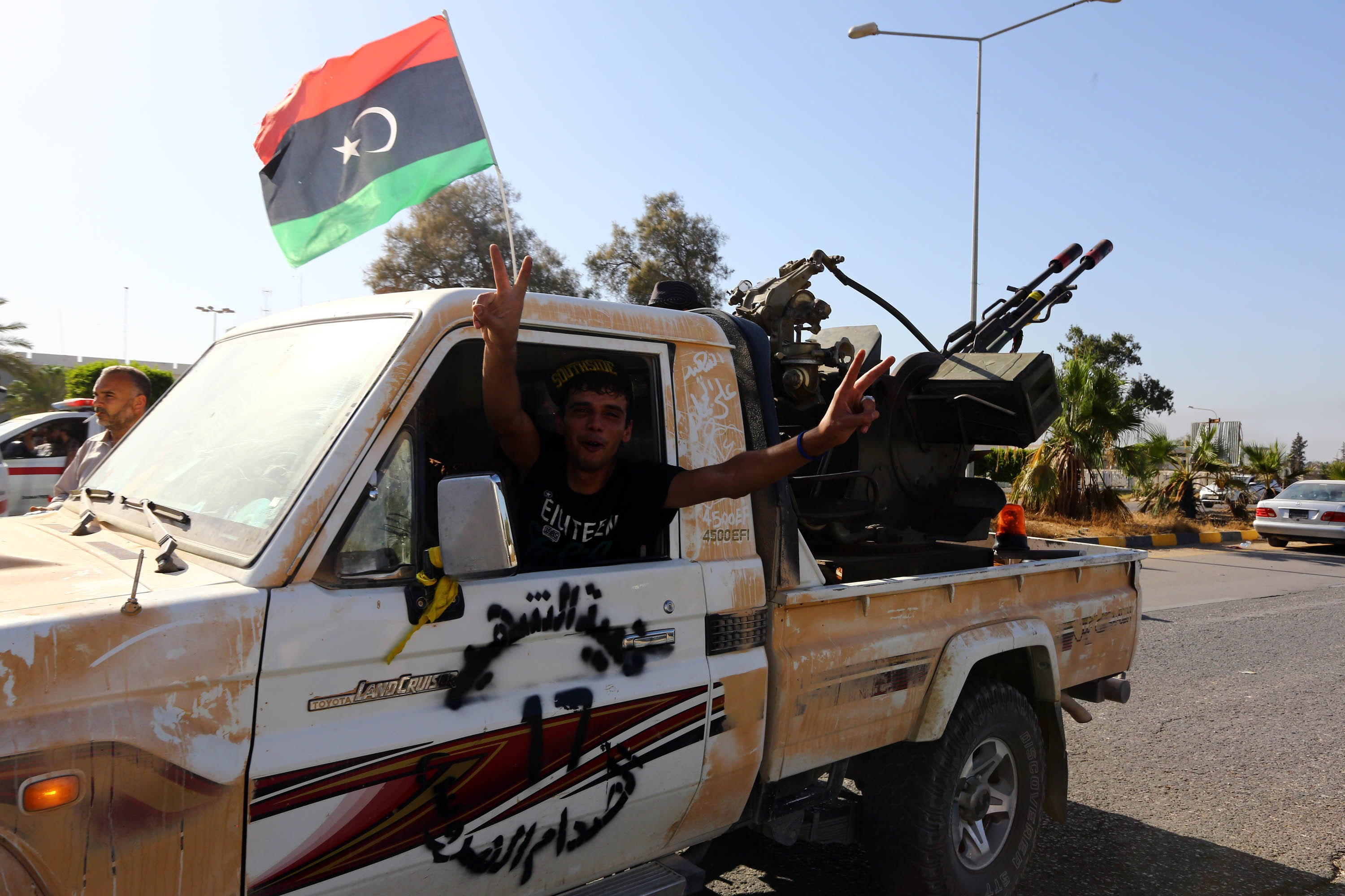 An Islamist fighter from the Fajr Libya (Libyan Dawn) coalition flashes the V sign for victory at the entrance of Tripoli international airport on August 24, 2014, after capturing it from Zintan force, allies of rogue general Khalifa Haftar, following many days of clashes.