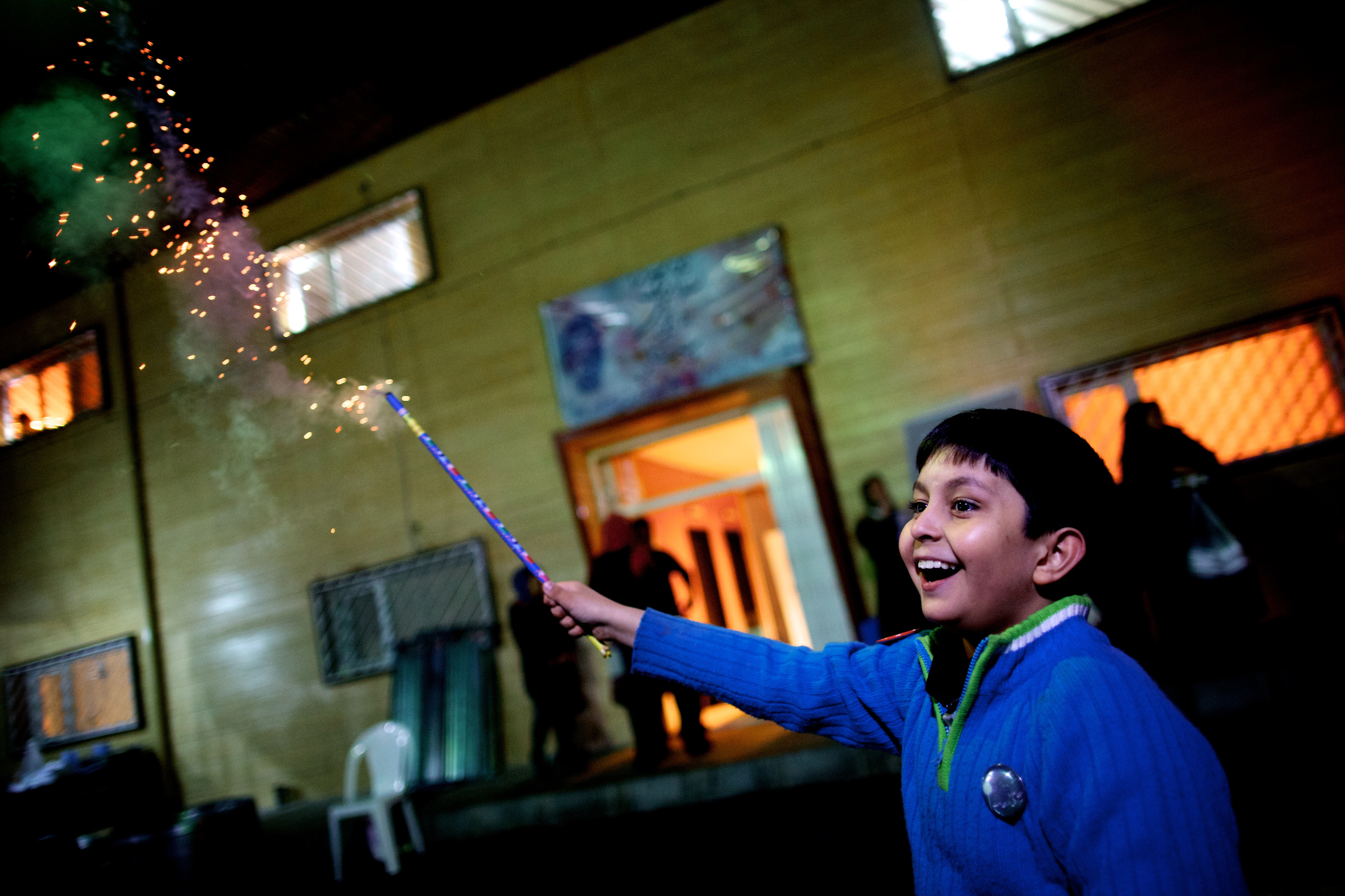 An Iranian boy holds a fire cracker in southern Tehran on March 19, 2013 during the Wednesday Fire feast, or Chaharshanbeh Soori, held annually on the last Wednesday eve before the Spring holiday of Noruz. The Iranian new year that begins on March 20 coincides with the first day of spring during which locals revive the Zoroastrian celebration of lighting a fire and dancing around the flame. AFP PHOTO/BEHROUZ MEHRI        (Photo credit should read BEHROUZ MEHRI/AFP/Getty Images)