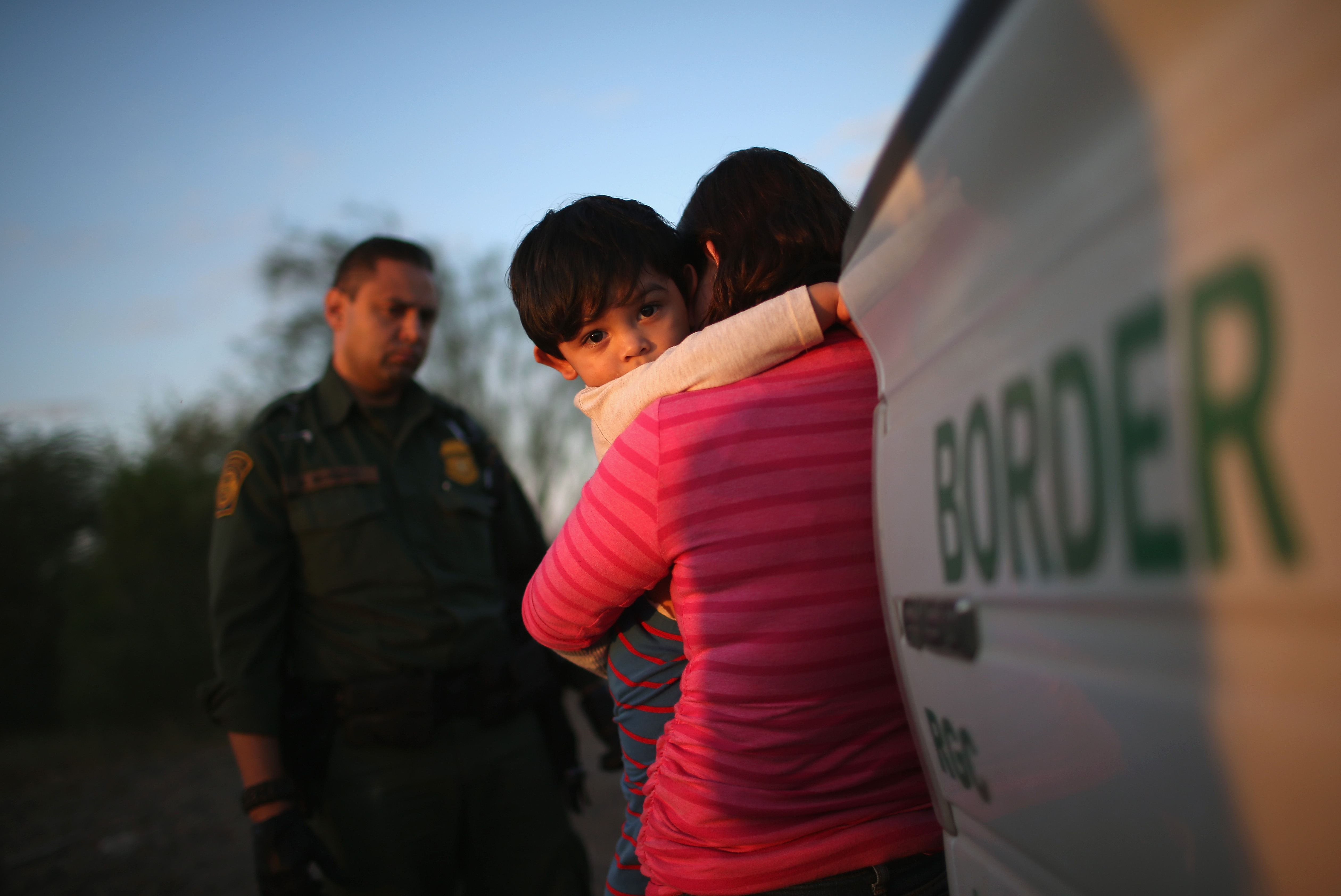 A one-year-old from El Salvador clings to his mother  ( John Moore/Getty Images)