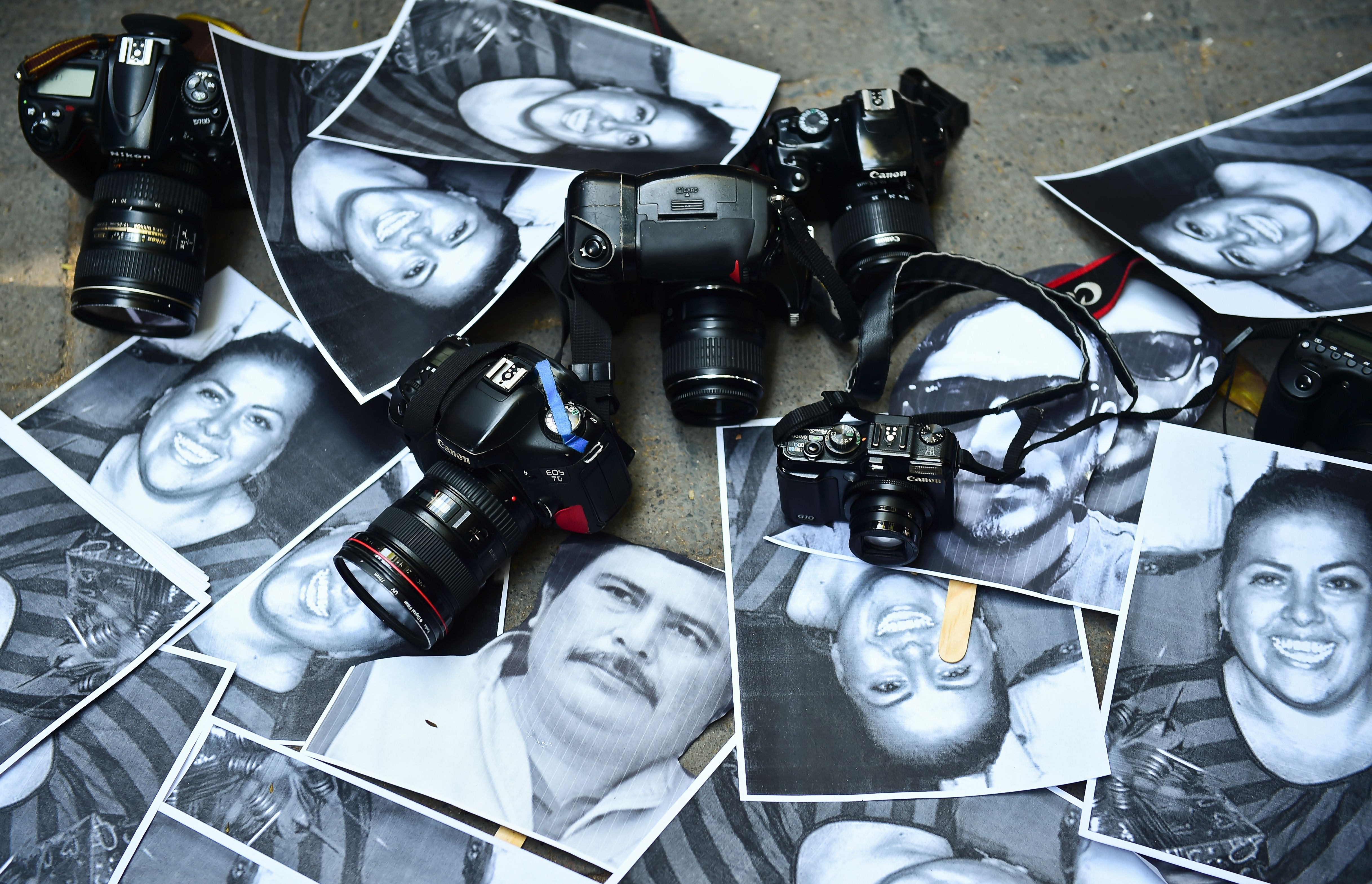 View of photos of killed journalists and cameras outside the Veracruz state representation office during a journalists protest in Mexico City on February 11, 2016. Mexican journalist Anabel Flores Salazar's funeral took place Wednesday after she was found killed at a road after being kidnapped Monday in Veracruz state, one of the most dangerous for journalists.  AFP PHOTO/RONALDO SCHEMIDT / AFP / RONALDO SCHEMIDT        (Photo credit should read RONALDO SCHEMIDT/AFP/Getty Images)