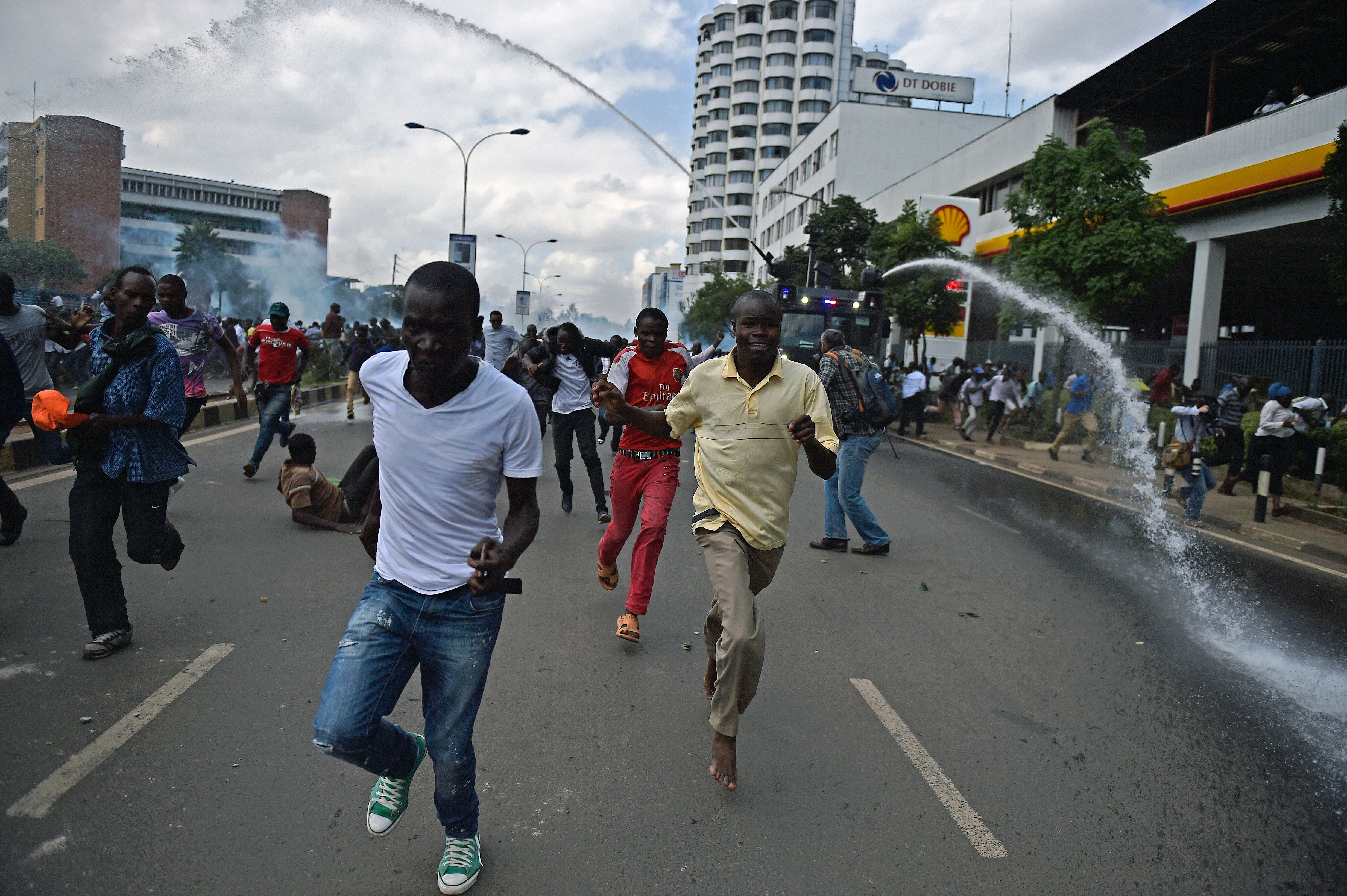 TOPSHOT - Protestors run from water canons after Kenya's opposition supporters demonstrated in Nairobi, on May 16, 2016. Opposition protestors led by former Prime Minister Raila Odinga had gathered outside the Indepedent Electoral and Boundaries Comission building to demand the dismissal of IEBC commissioners from office citing alleged bias towards the ruling Jubillee Alliance Party. / AFP / CARL DE SOUZA        (Photo credit should read CARL DE SOUZA/AFP/Getty Images)