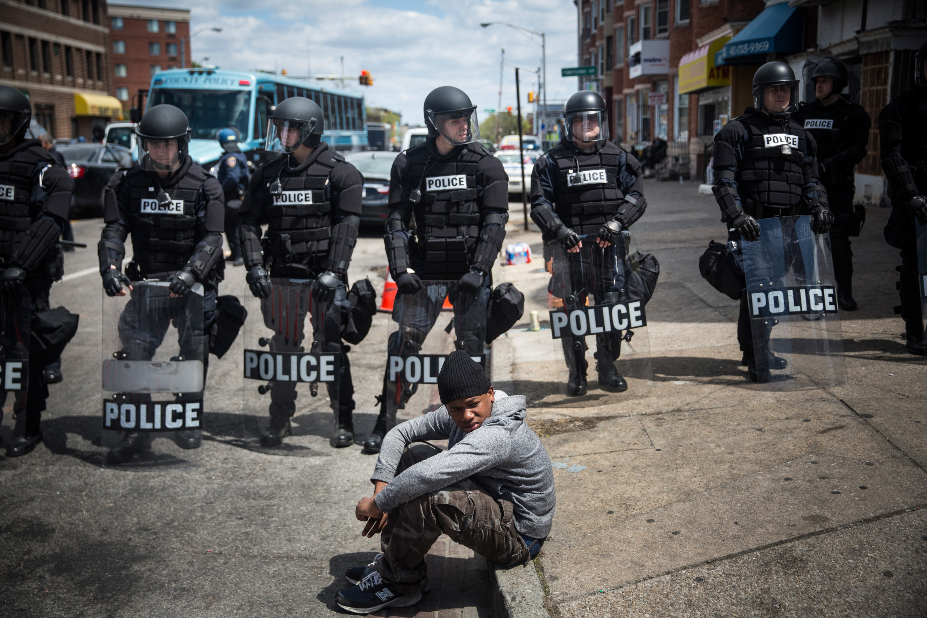 BALTIMORE, MD - APRIL 28: Daquan Green, age 17, sits on the curb while riot police stand guard near the CVS pharmacy that was set on fire yesterday during rioting after the funeral of Freddie Gray, on April 28, 2015 in Baltimore, Maryland. Gray, 25, was arrested for possessing a switch blade knife April 12 outside the Gilmor Houses housing project on Baltimore's west side. According to his attorney, Gray died a week later in the hospital from a severe spinal cord injury he received while in police custody. (Photo by Andrew Burton/Getty Images)