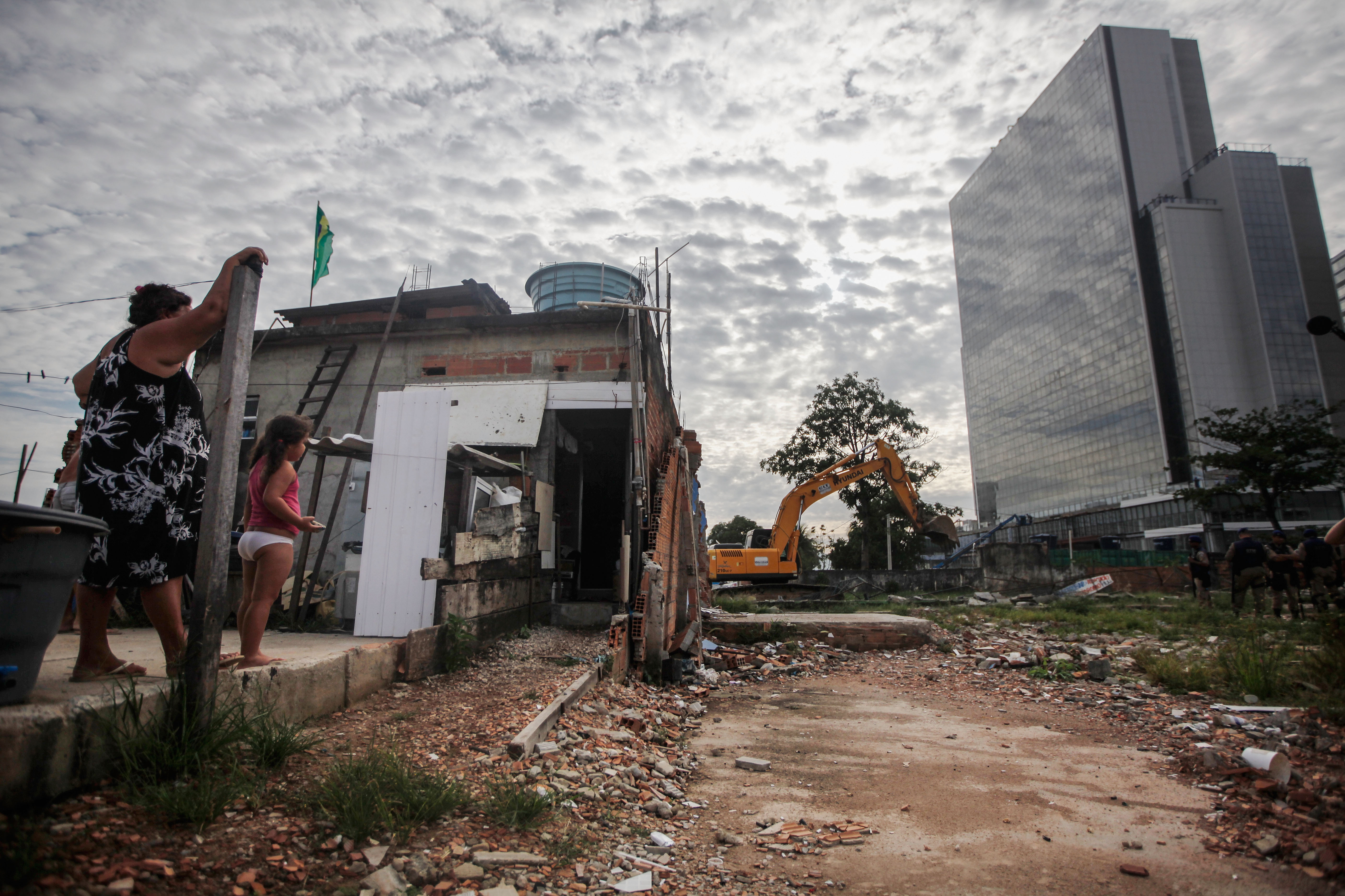 RIO DE JANEIRO, BRAZIL - FEBRUARY 24: Members of the Lopes family watch from their remaining home during the demolition of the neighboring residents association building in the mostly demolished Vila Autodromo favela community, with new Olympic Park construction standing (R), on February 24, 2016 in Rio de Janeiro, Brazil. Most residents of the favela community have moved out and had their properties demolished after receiving compensation for their homes which are located directly adjacent to the Olympic Park under construction for the Rio 2016 Olympic Games. A small fraction of remaining families from an original 700 or so in Vila Autodromo are resisting the controversial evictions and remain in the community. The favela sprang from an old fishing community and was considered one of the city's safest. Removals and demolitions have occurred in other Rio communities with tangential links to the games. (Photo by Mario Tama/Getty Images)