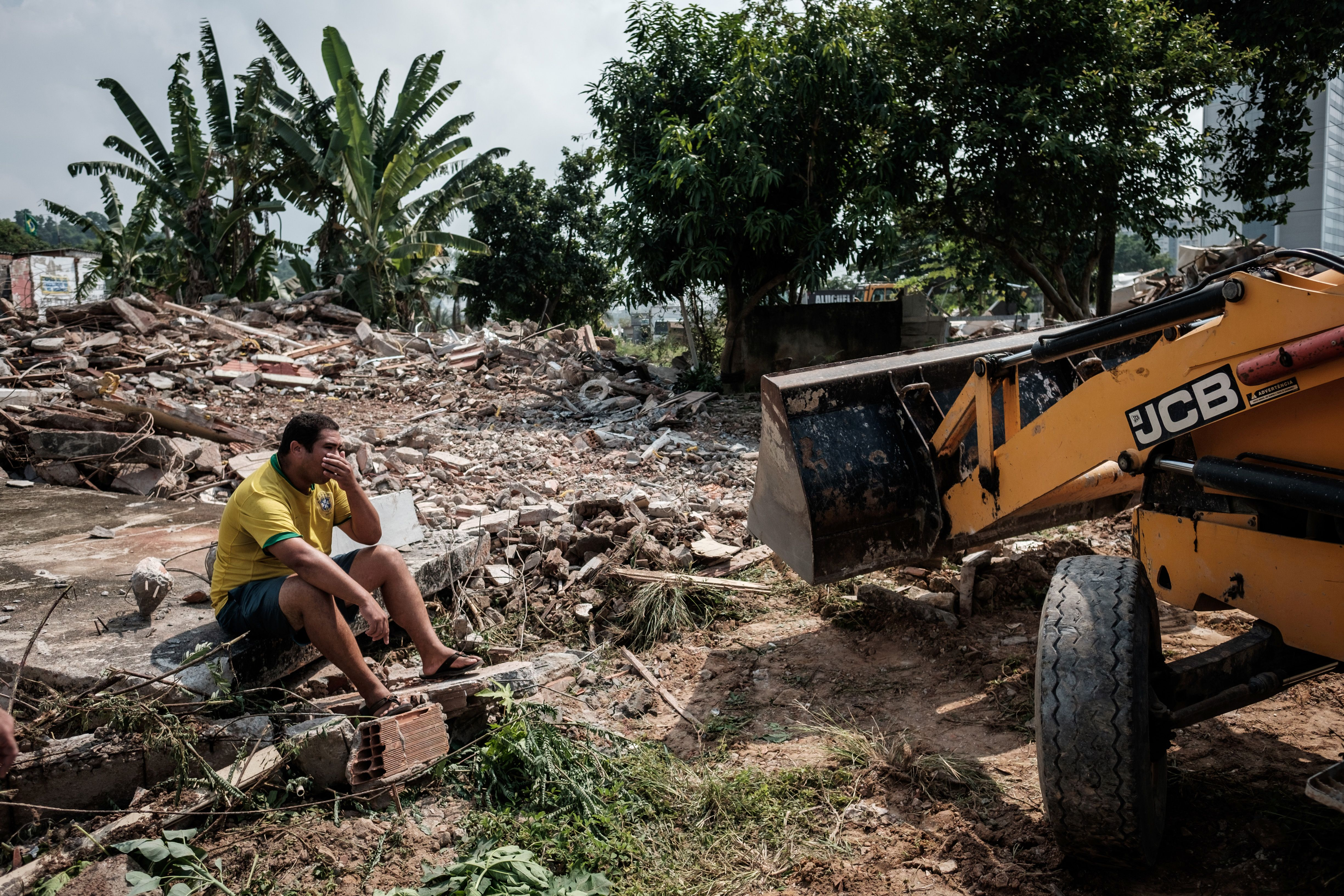 Brazilian Marcio Henrique sits on the ruins of a demolished house next door to his, at Rio de Janeiro's Vila Autodromo neighbourhood, near the construction site of the Olympic Park for the Rio 2016 Olympic Games, on March 8, 2016. Some families have refused to move out until they receive an eviction order by the municipal authorities. A passage connecting the Olympic Park and the Athletes Village is planned to be built on the site. AFP PHOTO / YASUYOSHI CHIBA / AFP / YASUYOSHI CHIBA (Photo credit should read YASUYOSHI CHIBA/AFP/Getty Images)