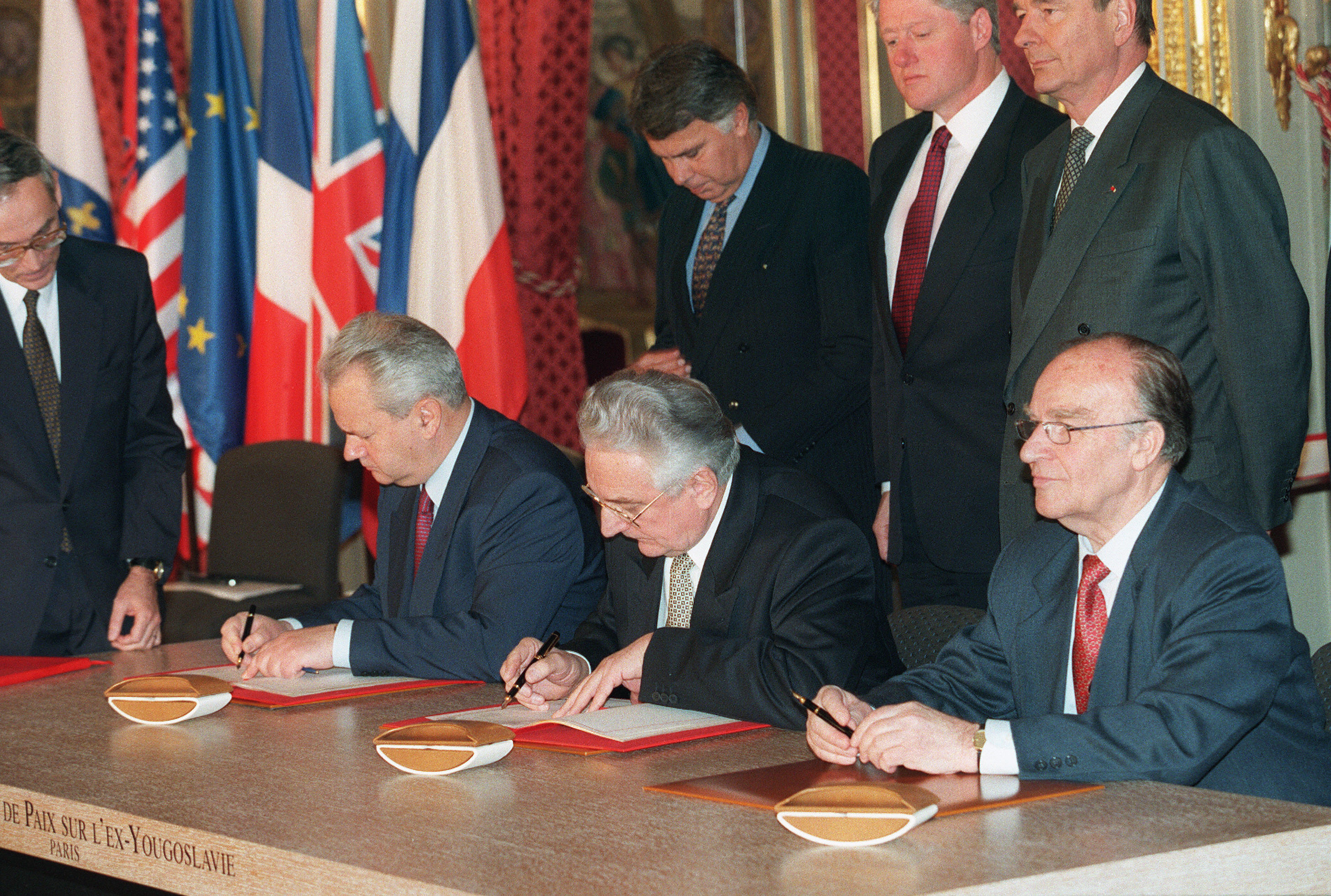 Paris, FRANCE: (FILES) This file picture taken 14 December 2005 at the Elysee Palace in Paris shows (1st Row L to R) Serbian president Slobodan Milosevic, Bosnian President Alija Izetbegovic (C) and Croatian President Franjo Tudjman signing the Dayton peace accord on Bosnia, as (2d row L to R) Spanish Prime Minister Felipe Gonzalez, US President Bill Clinton and French President Jacques Chirac look on. 14 December 2005 will mark the 10th anniversary of the signing of the Dayton peace agreement which ended more than three years of bloody inter-ethnic war and divided the country into a shaky system of separate but equal entities. AFP PHOTO/FILES/MICHEL GAGNE (Photo credit should read MICHEL GANGNE/AFP/Getty Images)