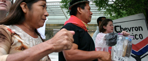 Emergildo Criollo, a leader from the Cofan tribe in Ecuador and Rita Maldonado, a Guanta community member at the demonstration outside the Chevron shareholder meeting. Behind them, an activist holds bottles of contaminated water. Photo: Amazon Watch